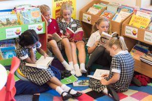 Prep school girls sitting on beanbags reading