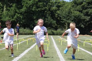 Three young children dressed in white sports kit running with small hurdles behind them