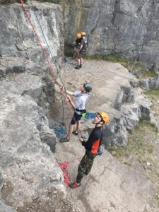 Students with ropes and harnesses looking up the face of rocks ready to climb