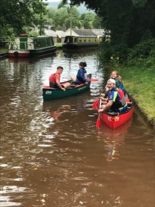 Sixth Form students canoeing down a canal