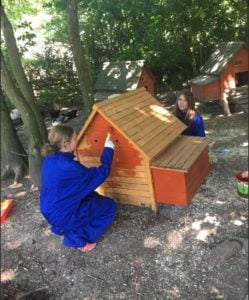 Two girls painting a chicken hut on the school farm