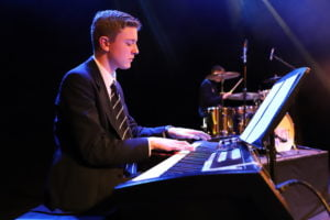 Senior boy playing the keyboard on stage under a spotlight