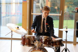 Senior school drummer playing in the New Bury Theatre foyer